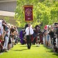 The Westmont banner, marking the college's 75th anniversary, leads the procession