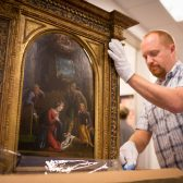 "Chris Rupp, collections manager of Westmont Museum of Art, carefully uncrates Tisi's ""La Nativité"""