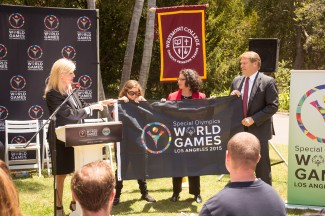 Joann Klonowski, Special Olympics world games, vice president of host town, presents the Special Olympics flag to Savannah Barclay, Special Olympics Southern California global messenger, Santa Barbara mayor Helene Schneider, and Westmont president Gayle D. Beebe (left to right).