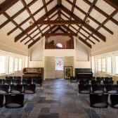 Warm light basks in the renovated prayer chapel. These temporary chairs will be replaced with wood-framed, fabric-covered chairs