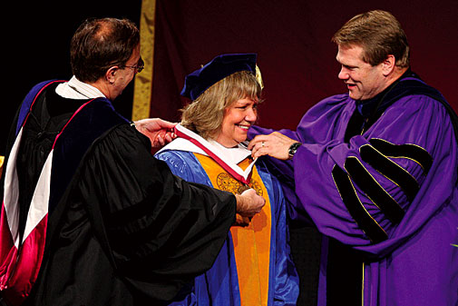 Judy L. Larson receives an honorary metal from board of trustees chair, Steve Stong and President Gayle Beebe